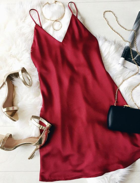 red slip dress on fur rug with shoes bags and necklace