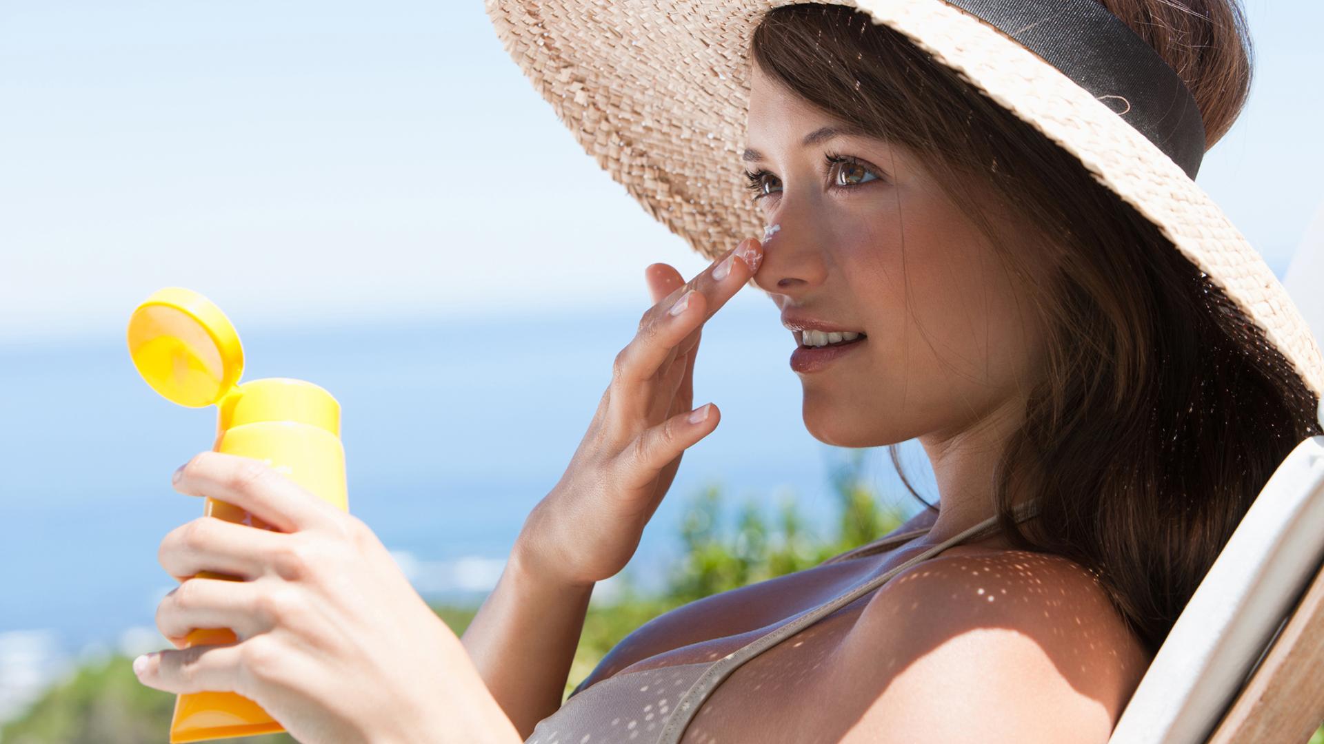 women in hat on beach putting on suncscreen
